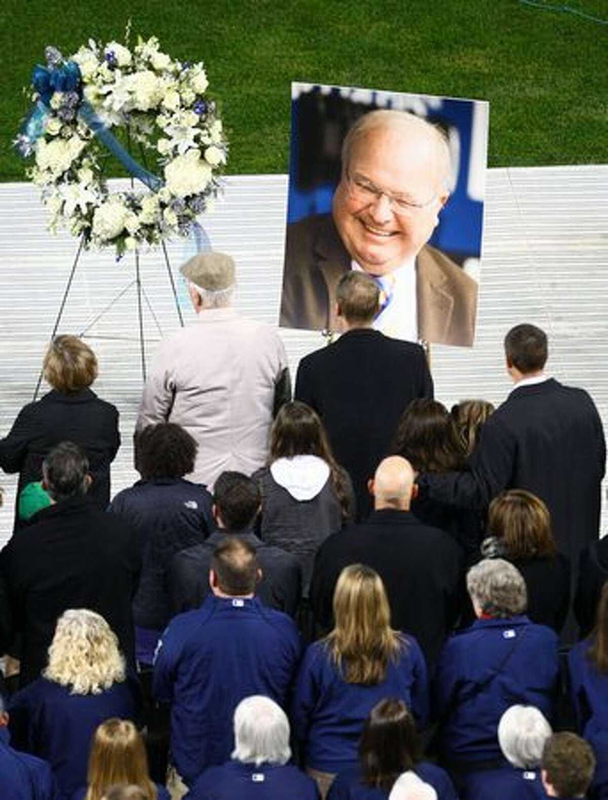 People stand during the national anthem at a celebration of life ceremony for Seattle Mariners broadcaster Dave Niehaus.