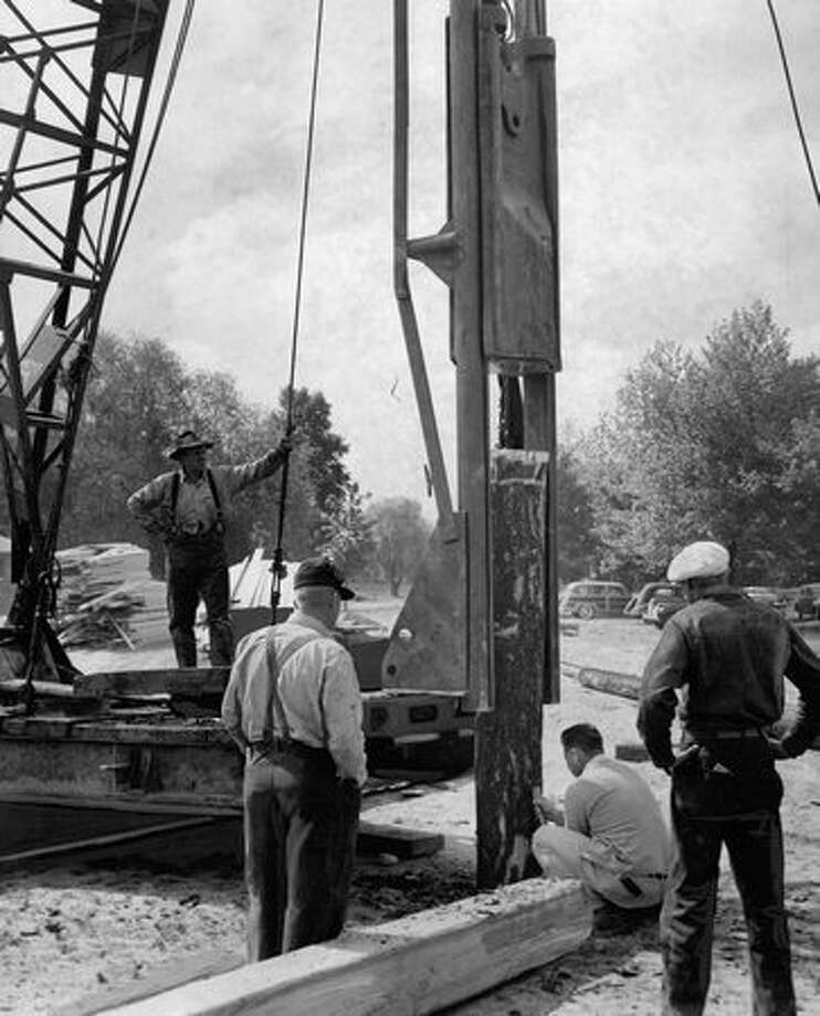 Workers prepare to drive the first pile for the Green Lake Aqua Theater, June 1950. Photo: P-I File