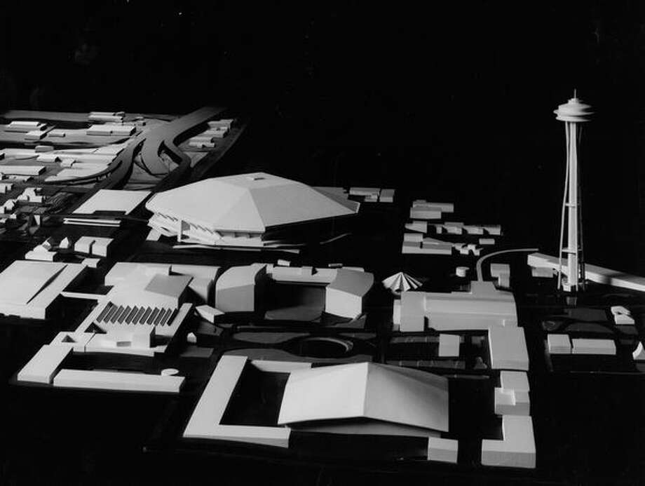 The December 1969 photo caption read: View of domed-stadium model, looking east from point on west side of Seattle Center. Model shows how Bay Freeway will curve along east side of stadium and how ramps off Bay Freeway will feed directly into parking garage on north side of Mercer across from stadium. Coliseum [now KeyArena] is in center foreground; Opera House complex and existing Mercer Street parking garage at left center. Photo: P-I File
