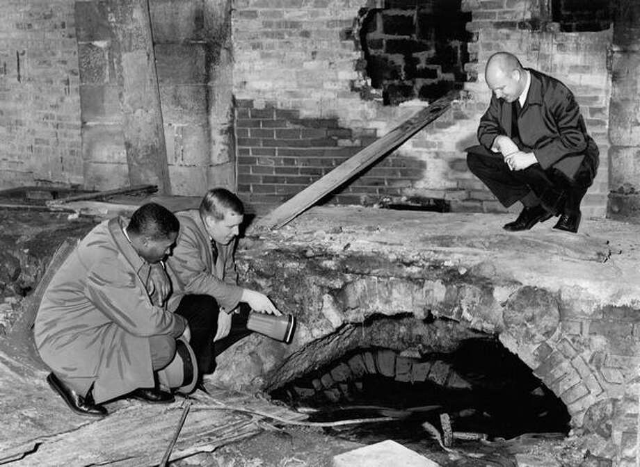 The January 1965 photo caption reads: A subterranean foot bridge used by Seattle's pioneers before the 1889 fire is examined by three members of the Junior Chamber of Commerce. They are, left to right, Luther Carr, Bob Ashley (holding flashlight) and Bill McKinley. The old bridge, at level of a former city street, stands in the basement of the Cannery Worker's Union at 213 S. Main St. Photo: P-I File