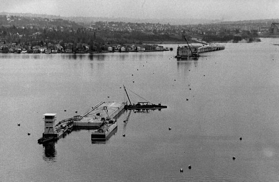 The March 1963 photo caption read: This group of five pontoons comprising the West draw unit of new Evergreen Floating Bridge, is being anchored in Lake Washington. Photo: P-I File