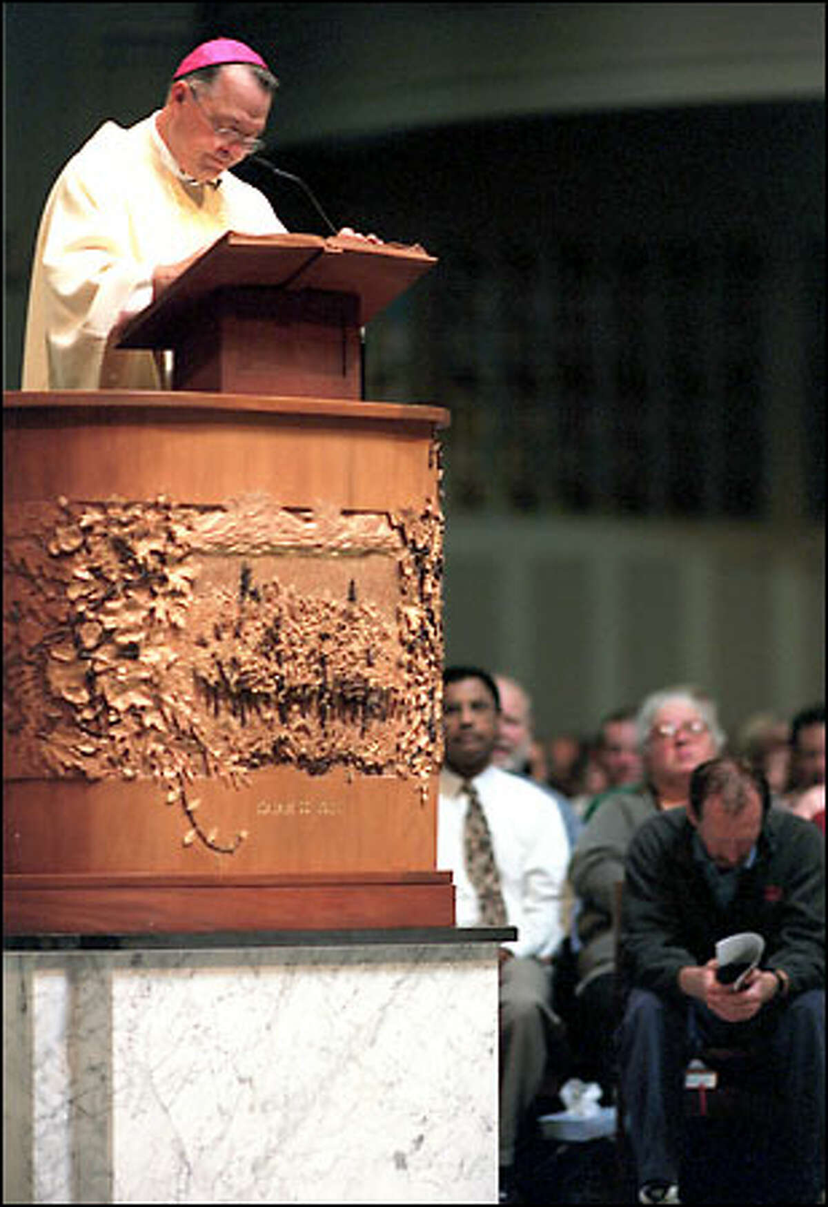 File -- After the 9/11 attacks, Archbishop Alexander Brunett tries to console Seattleites during his sermon at St. James Cathedral. Hundreds packed the church.