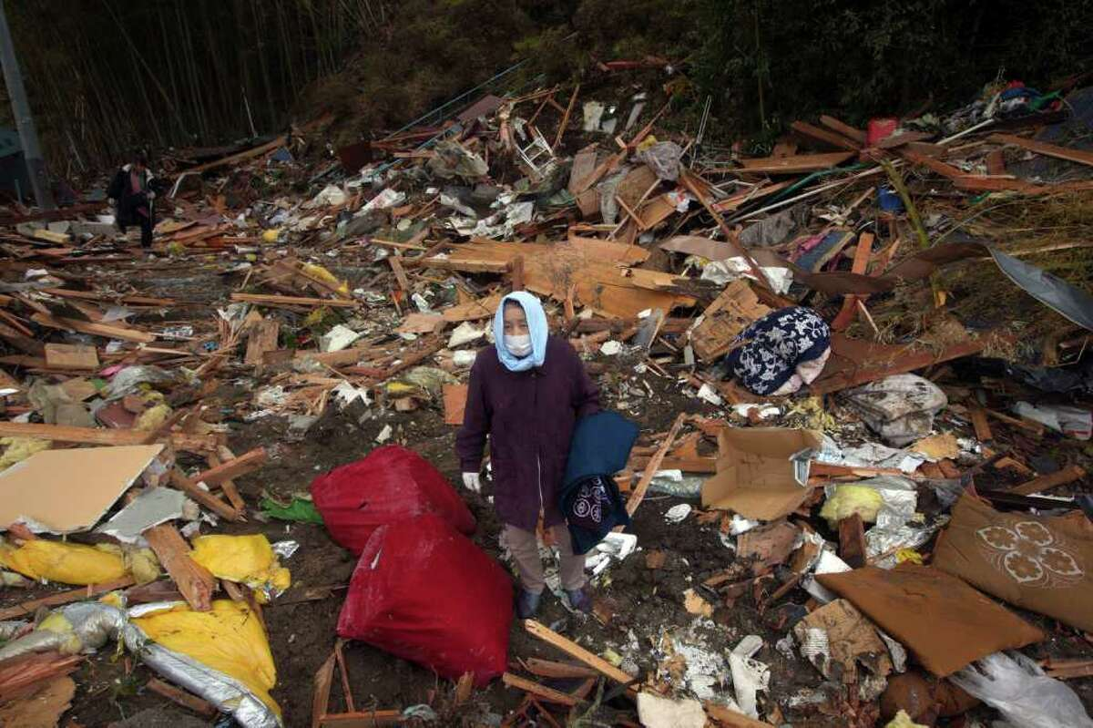 Kiyoko Kin searches through the rubble of part of her house that was washed away from the tsunami March 26, 2011 in Rikuzentakata, Japan. More than two weeks after the magnitude 9 earthquake and tsunami struck Japan the death toll has risen to over 10,000 dead with still thousands missing and the expectation is that it will end up well over 20,000. Presently the country is still struggling to repair a damaged nuclear power plant that has caused tremendous problems, evacuations, and now tainted water supply in the Tokyo area causing more panic buying of bottled water.