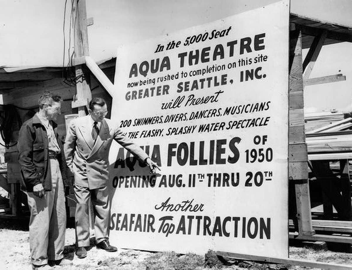 Clarence Rushton, superintendent of the Aqua Theater construction project listens to Walter A. Van Camp, managing diretor of Greater Seattle, Inc., after the two put the sign in place in June 1950. Rushton's crew needed the 5,000 Aqua Theater completed in time for the gala opening of
