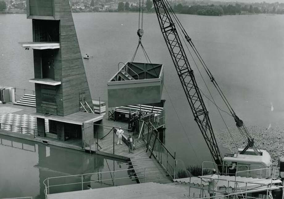 An 8-ton steel structure that was used as a sinken orchestra pit is lifted into the Aqua Theater by a giant mobile crane, June 1958. Gustavo Stern, musical director of the Greater Seattle musicals, watches from the right foreground. Photo: P-I File
