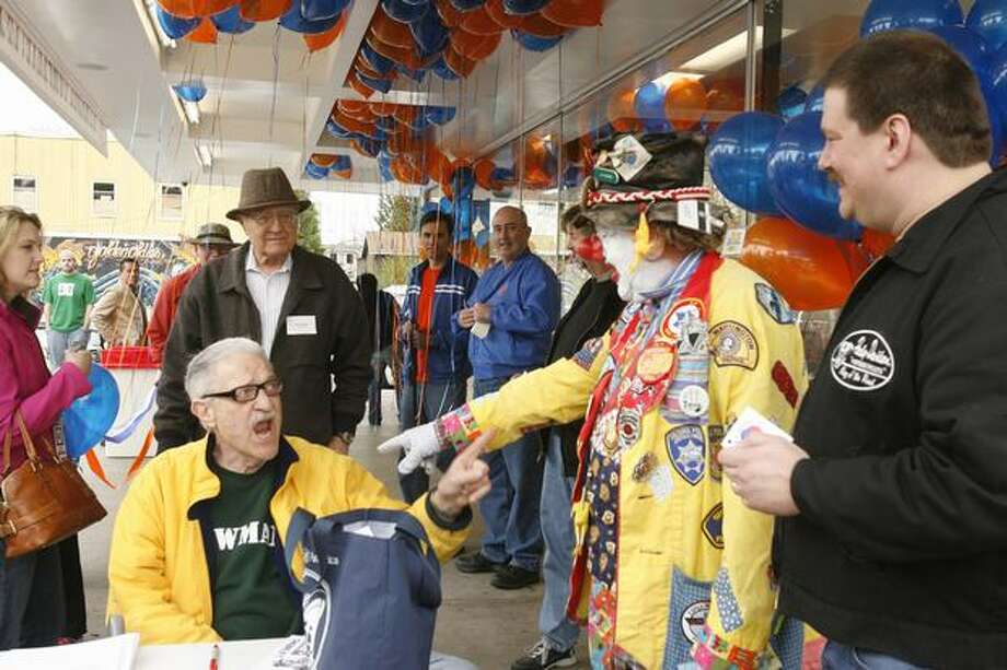"Bob Newman, sitting, and J.P. Patches, at the 2007 celebration for the expanded Dick's Drive-In on Northeast 45th Street. Former ""Almost Live!"" host John Keister is behind Newman in blue. (Grant M. Haller/Seattlepi.com) Photo: P-I File"