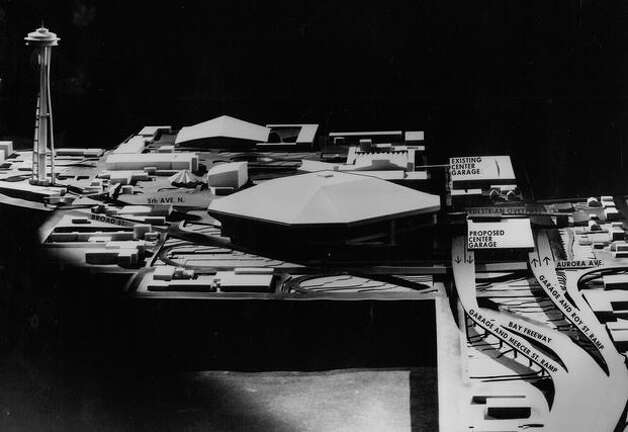 The December 1969 photo caption read: Model of King County domed stadium and Seattle Center complex, looking west along Mercer Street. Note how off-ramps from Bay Freeway lead directly into parking garage. Bay Freeway itself curves southwest under Broad Street along southeast side of stadium. Photo: P-I File