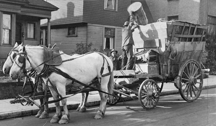 The caption for this photo reads: In 1915, garbage disposal in Seattle was a problem. Here is Rig 71 of the Health and Sanitation Department: a steel-rim wheeled heavy cart, two disposal men, and a pair of patient white horses probably named Pat and Mike. As the wagon filled, slatted sides were erected and lined with old burlap, and the garbage was taken to the dump. Photo: P-I File