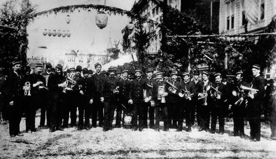The photo caption reads: Seattle's first band at the time of the barbecue in September 1883. This picture was taken at the corner of First Avenue South and (South) Jackson Street. Photo: P-I File