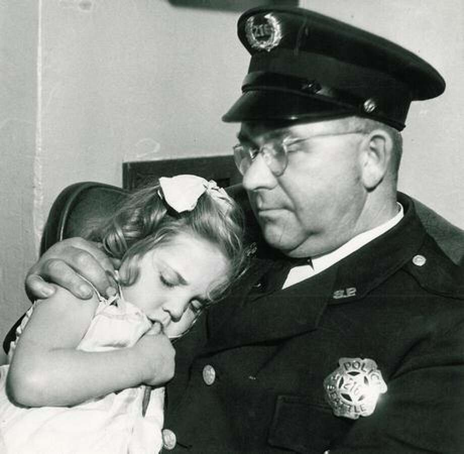 The long arm of the law--officer holds a sleeping child. Photo: P-I File
