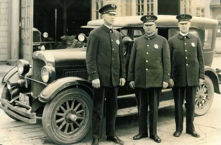 "This relay of three drivers is mighty proud of this Studebaker standard six phaeton, West Seattle police ""prowler"" car, and Seattle's latest addition to the Studebaker 100,000-mile Club. October 4, 1926. Photo: P-I File"