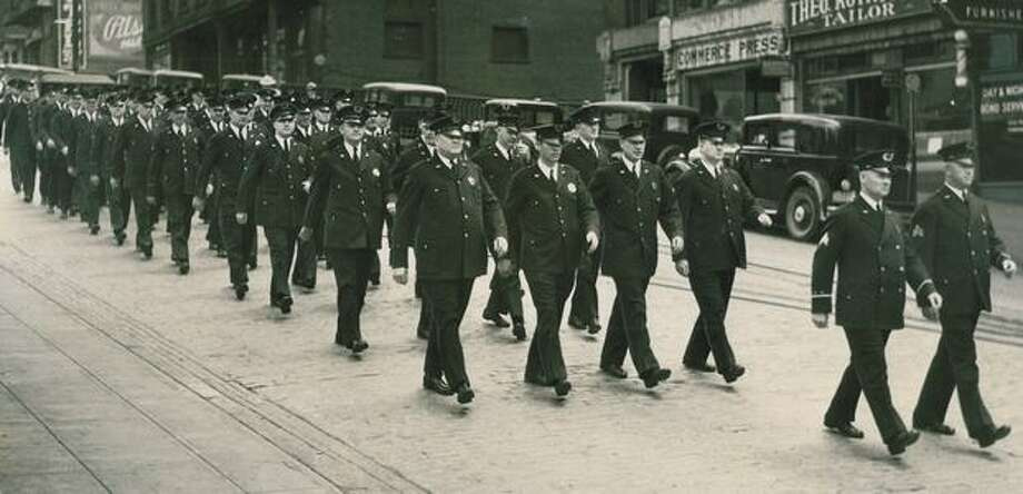 "Chief George F. Howard's order that Seattle police are to live up to the title, ""The City's Finest,"" was beginning to bear fruit yesterday. Here is the afternoon patrol, swinging down the avenue like a crack military unit. June 7, 1934. Photo: P-I File"