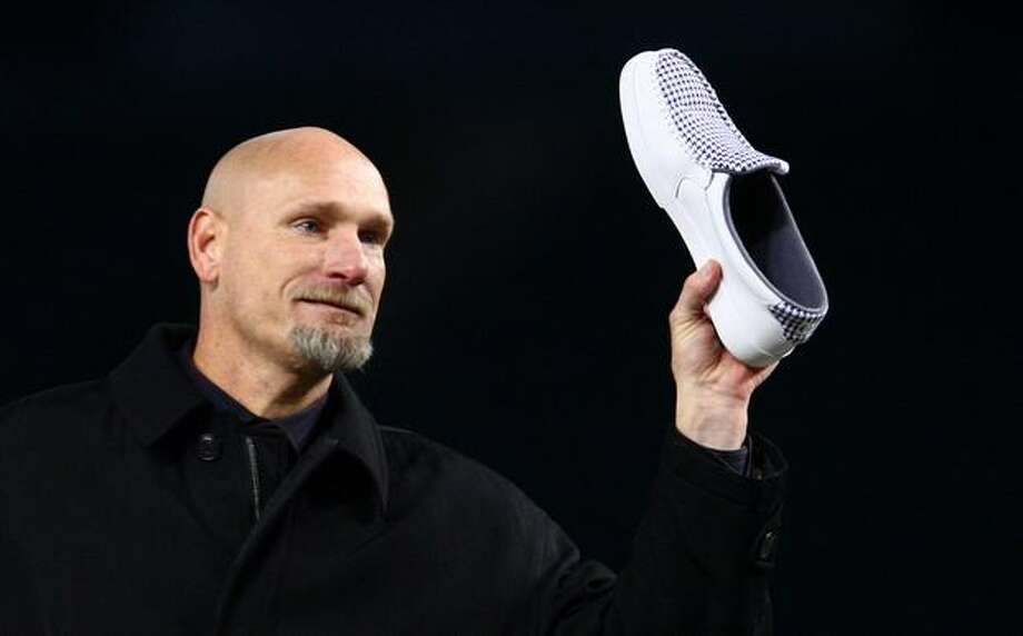 Former Mariner Jay Buhner shows a shoe he wore in honor of Dave Niehaus during a celebration of life ceremony for the longtime Seattle Mariners broadcaster on Saturday at Safeco Field. Buhner told a story how he once played a joke on Niehuas, using red shoe polish on Niehause's white shoes, turning them pink. The voice of the Mariners passed away last month. Photo: Joshua Trujillo, Seattlepi.com