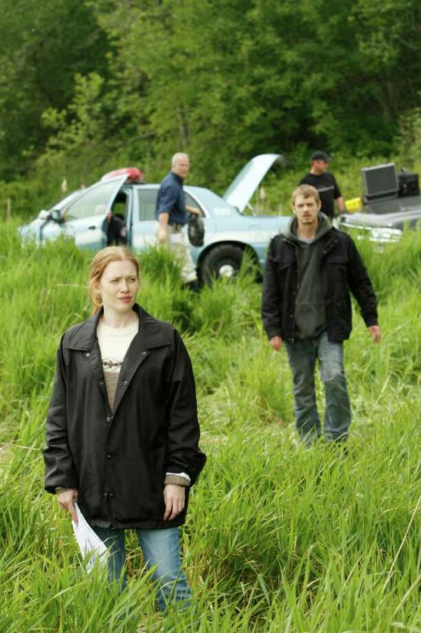 """In this publicity image released by AMC, Mireille Enos portrays Detective Sarah Linden and Joel Kinnaman portrays Detective Stephen Holder, right, in a scene from the AMC original series """"The Killing,"""" premiering April 3, 2011 at 9 p.m. EST. (AP Photo/AMC, Chris Large) Photo: Chris Large, HO / San Antonio Express-News"""