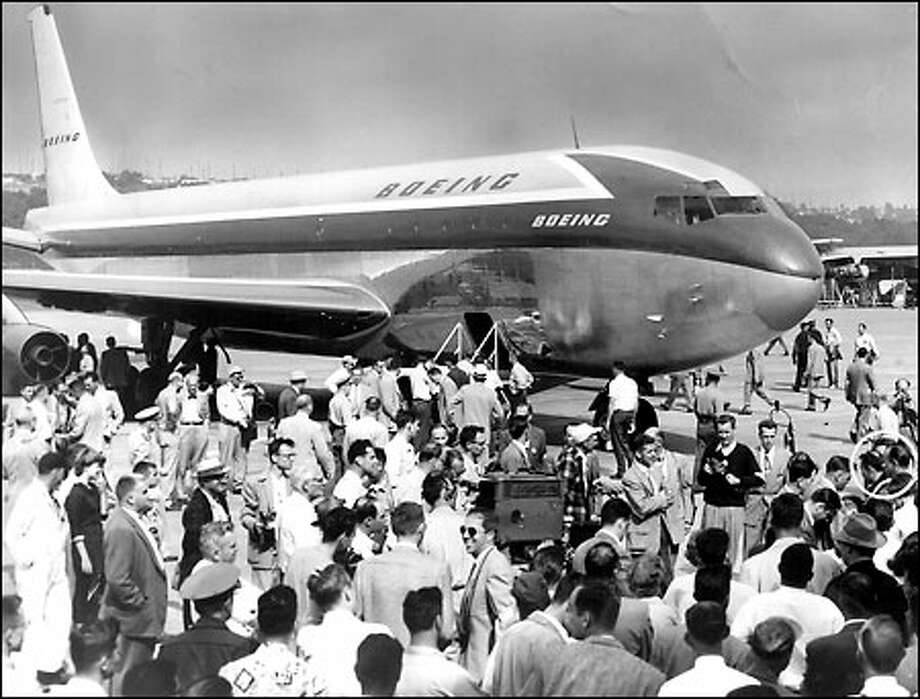 Boeing in the commercial jet market, 1954: Test pilots, circled at far right, are surrounded by reporters, photographers and well-wishers after completion of a Boeing 707 test flight at Seattle's Boeing Field. Production of the huge transport began a long string of efficient commercial jet planes for The Boeing Co. Photo: Seattle Post-Intelligencer