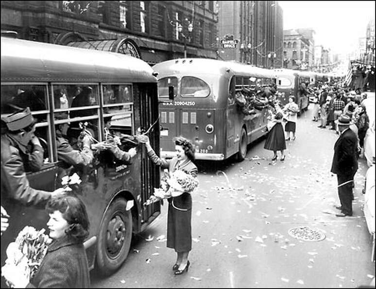 Welcome Lane, c.1953: Troops coming home from the Korean War are met by crowds, confetti and flowers