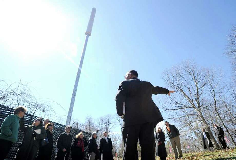 """Foreground, Carlo Centore of Centek Engineering of Branford, Conn., explains plans for a new cell tower that would replace the exisiting 70-foot AT&T """"flag pole""""-style cell tower, pictured. The Connecticut Siting Council and interested parties listen during a tour of the site of the proposed Verizon Wireless 77-foot cell tower, at 36 Ritch Ave., Byram, Tuesday afternoon, March 29, 2011. The new tower would be designed to look like a pine tree. Photo: Bob Luckey / Greenwich Time"""