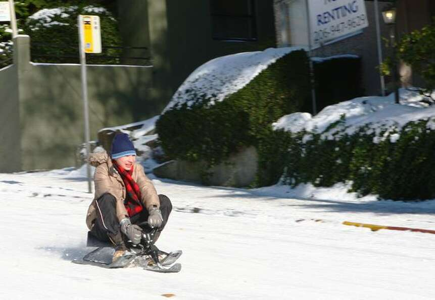 A sledder heads down Queen Anne Hill Tuesday after the road was closed due to snow and ice.