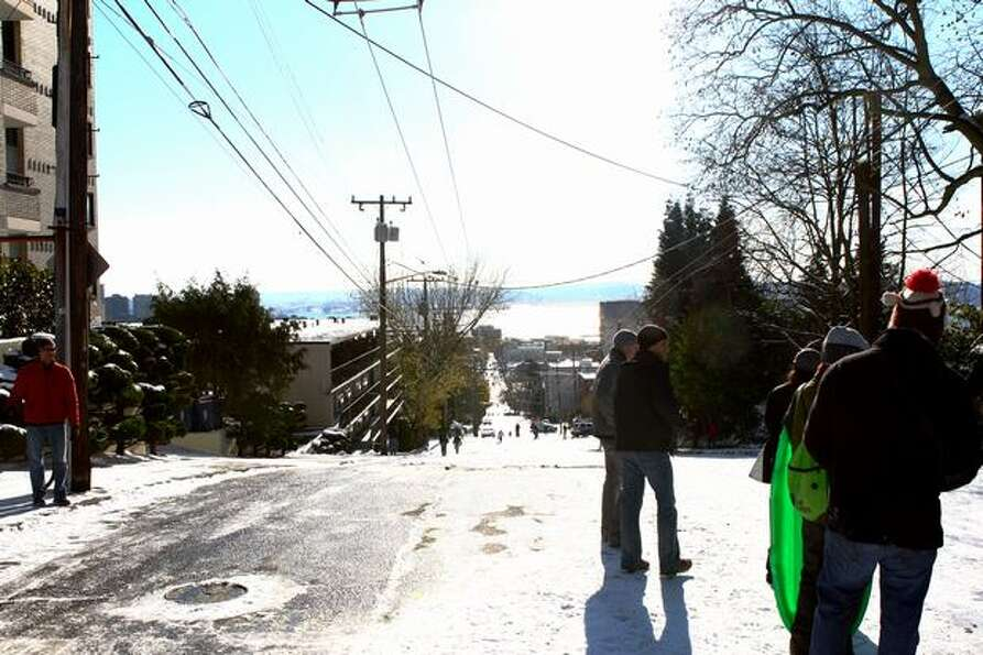 Sledders wait atop Queen Anne Hill to descend down a closed Seattle street.