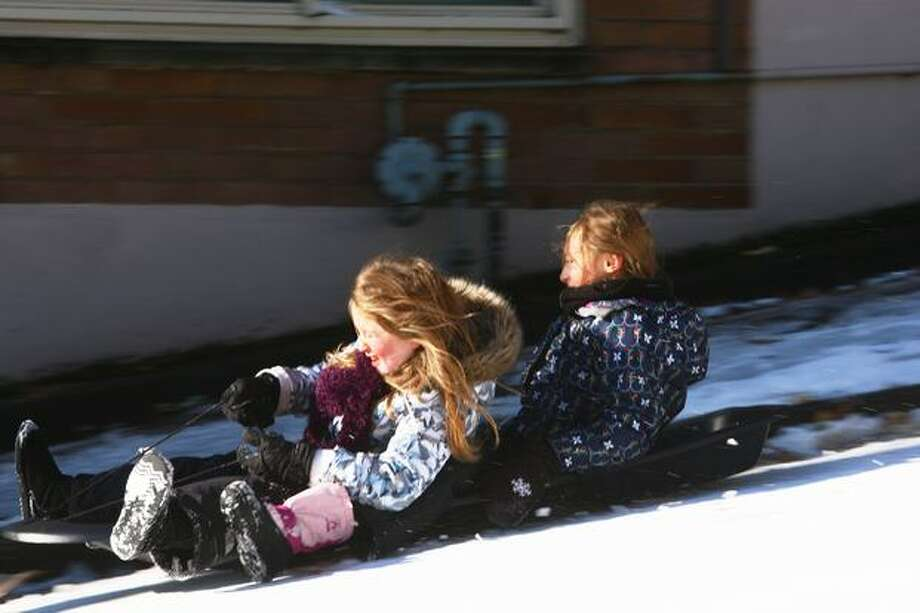 Darrein Cole, 8, and Ellis Stock, 9, slide down Queen Anne Avenue North. The road was closed Tuesday due to snow and ice. Photo: Levi Pulkkinen, Seattlepi.com
