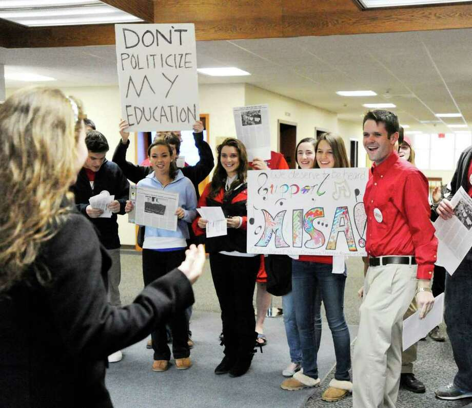 Greenwich High School junior Kim Rogers, 16, second from right, holds up a support MISA sign as she stands with fellow students in the lobby of Greenwich Town Hall prior to a Board of Estimate and Taxation public hearing on the town budget, Tuesday night, March 29, 2011.  The MISA project is a proposed new music and instruction space & auditorium for Greenwich High School.  Rogers said she is involved in theater at Greenwich High School and wants a new facility. Photo: Bob Luckey / Greenwich Time