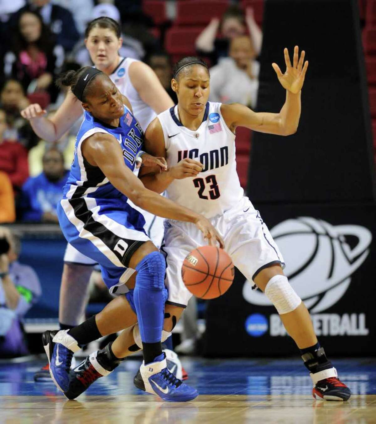 Duke's Karima Christmas, left, battles for control of the ball against Connecticut's Maya Moore (13) in the first half of an NCAA women's college basketball tournament regional final, Tuesday, March 29, 2011, in Philadelphia. (AP Photo/Barbara Johnston)