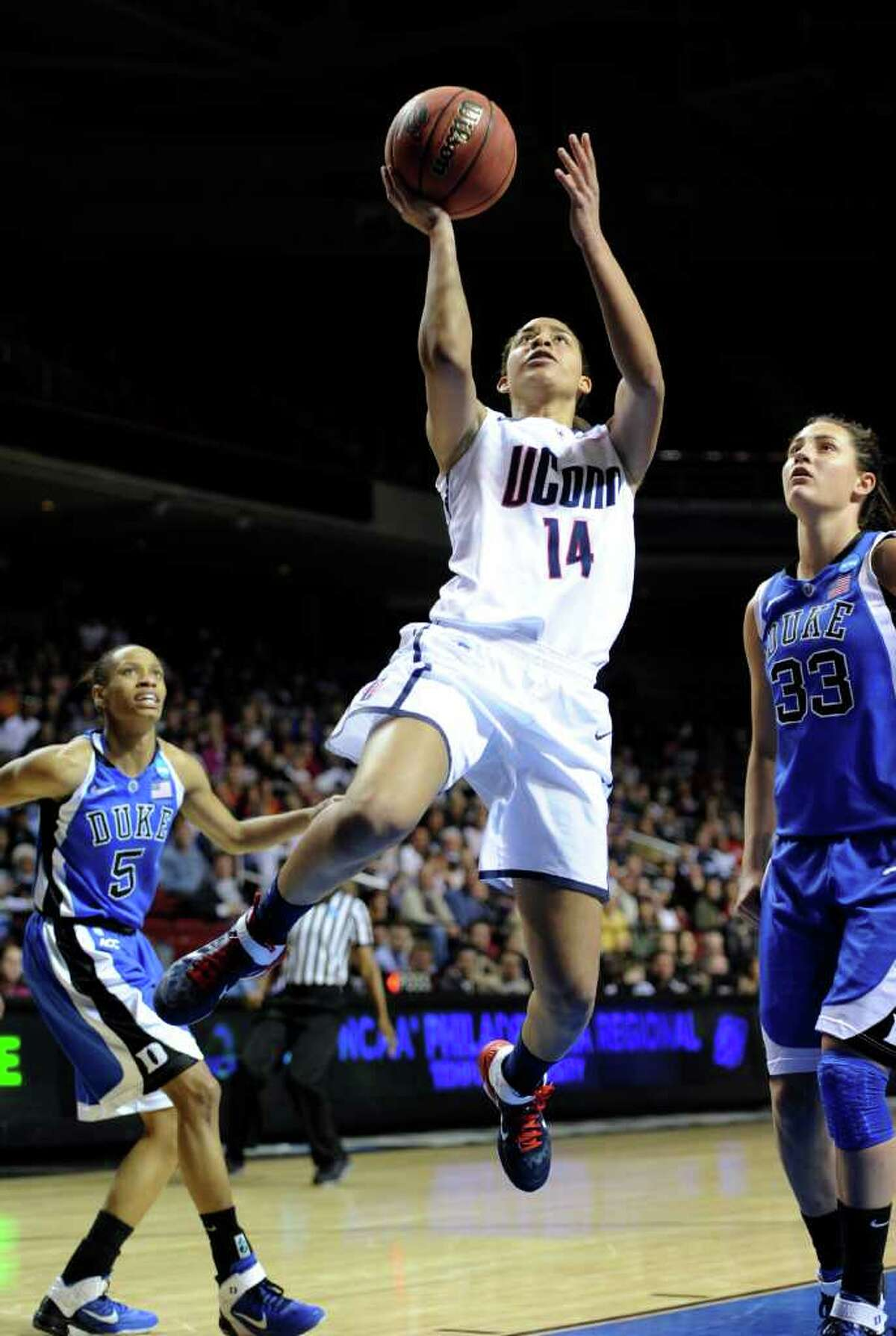 Connecticut's Bria Hartley (14) shoots past Duke's Jasmine Thomas (5) and Haley Peters in the first half of an NCAA women's college basketball tournament regional final game, Tuesday, March 29, 2011, in Philadelphia. (AP Photo/Barbara Johnston)