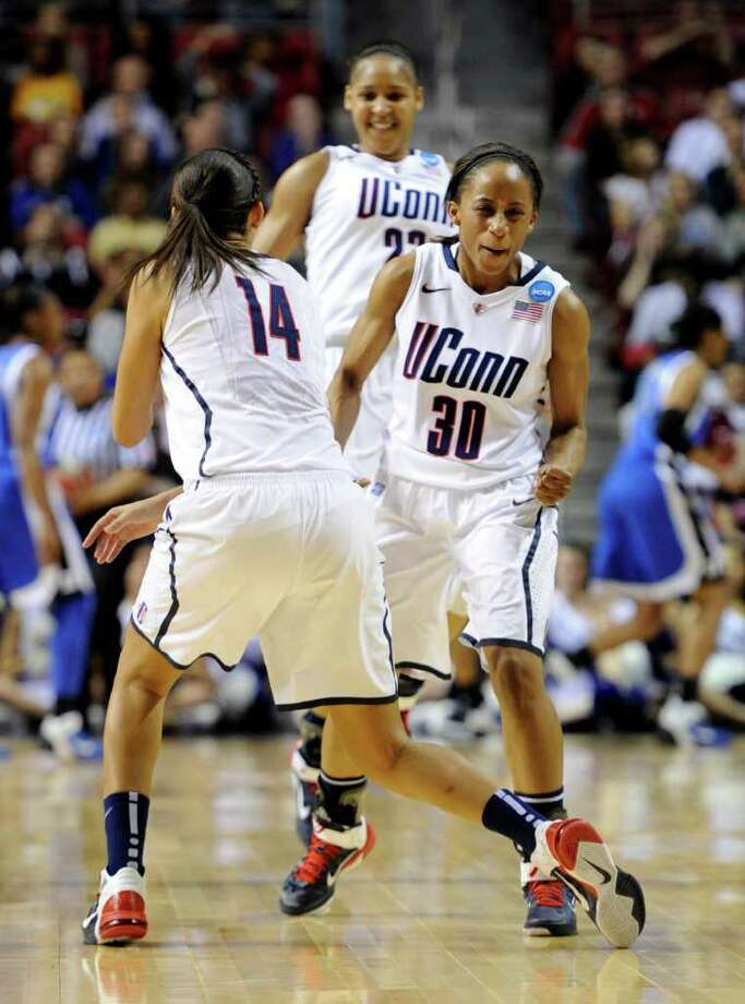 Connecticut guards Bria Hartley (14), Lorin Dixon and forward Maya Moore, rear, celebrate at the buzzer for the end of the first half against Duke during an NCAA women's college basketball tournament regional final game, Tuesday, March 29, 2011, in Philadelphia. (AP Photo/Barbara Johnston) Photo: AP