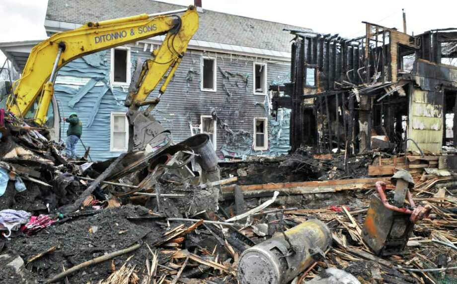 A crew from Ditonno and Sons Demolition of Albany waits for permission to finish razing a burned-ot home at 923 Stanley St. in Schenectady Tuesday morning March 29, 2011.   (John Carl D'Annibale / Times Union) Photo: John Carl D'Annibale