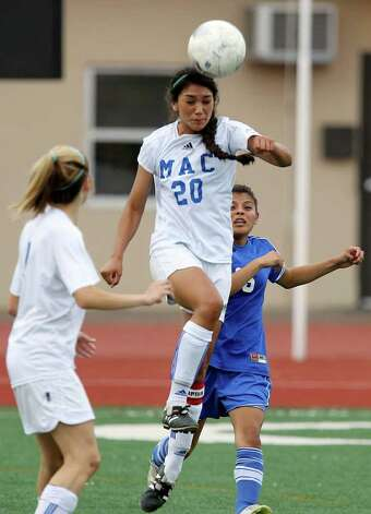 MacArthur's Anja Rosales (20) gets the advantage on a header against New Braunfels' Whitney Cortez (right) in girls soccer at Comalander Stadium on Tuesday, March 29, 2011. Photo: Kin Man Hui/kmhui@express-news.net / San Antonio Express-News NFS