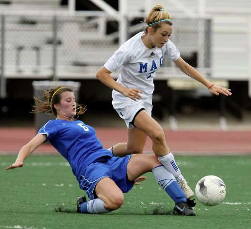 MacArthur's Brianna Livecchi (right) gets tripped while going for the ball against New Braunfels' Morgan Mosegard (05) in girls soccer at Comalander Stadium on Tuesday, March 29, 2011. Photo: Kin Man Hui/kmhui@express-news.net / San Antonio Express-News NFS