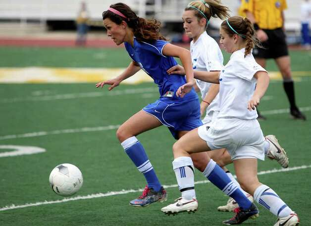 New Braunfels' Bonnie Charlton (left) pushes the ball upfield against MacArthur's Brianna Livecchi and Megan Baer (right) in girls soccer at Comalander Stadium on Tuesday, March 29, 2011. Photo: Kin Man Hui/kmhui@express-news.net / San Antonio Express-News NFS