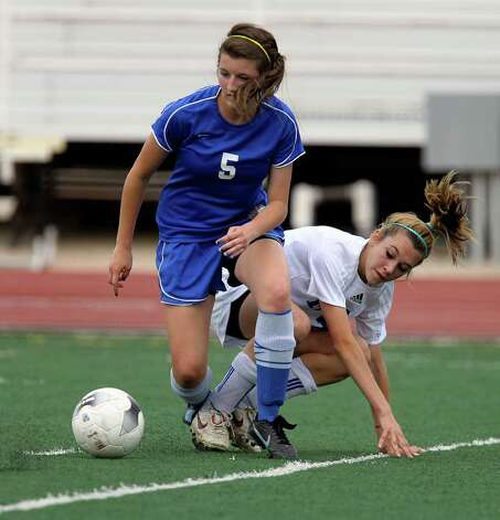 New Braunfels' Morgan Mosegard (05) and MacArthur's Brianna Livecchi (07) get tangled while going for the ball in girls soccer at Comalander Stadium on Tuesday, March 29, 2011. Photo: Kin Man Hui/kmhui@express-news.net / San Antonio Express-News NFS