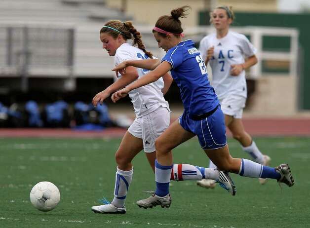 MacArthur's Kelsey Falcone (left) and New Braunfels' Morgan Hill chase down a pass in girls soccer at Comalander Stadium on Tuesday, March 29, 2011. Photo: Kin Man Hui/kmhui@express-news.net / San Antonio Express-News NFS