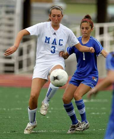 MacArthur's Brandy Mercado (03) and New Braunfels' Taylor Sanchez (01) compete for the ball in girls soccer at Comalander Stadium on Tuesday, March 29, 2011. Photo: Kin Man Hui/kmhui@express-news.net / San Antonio Express-News NFS