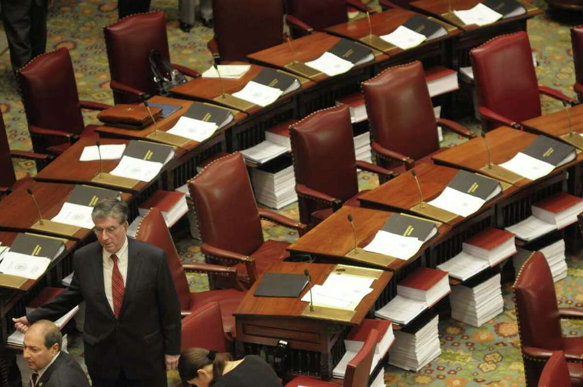 Senator Tom Libous, left, and Senator Neil Breslin, 2nd from left, talk on the floor of the New York State Senate before the start of a Senate session on Tuesday, March 29, 2011. The stacks of paper beneath the Senator' desks contain budget bills that will be voted on. (Paul Buckowski / Times Union)