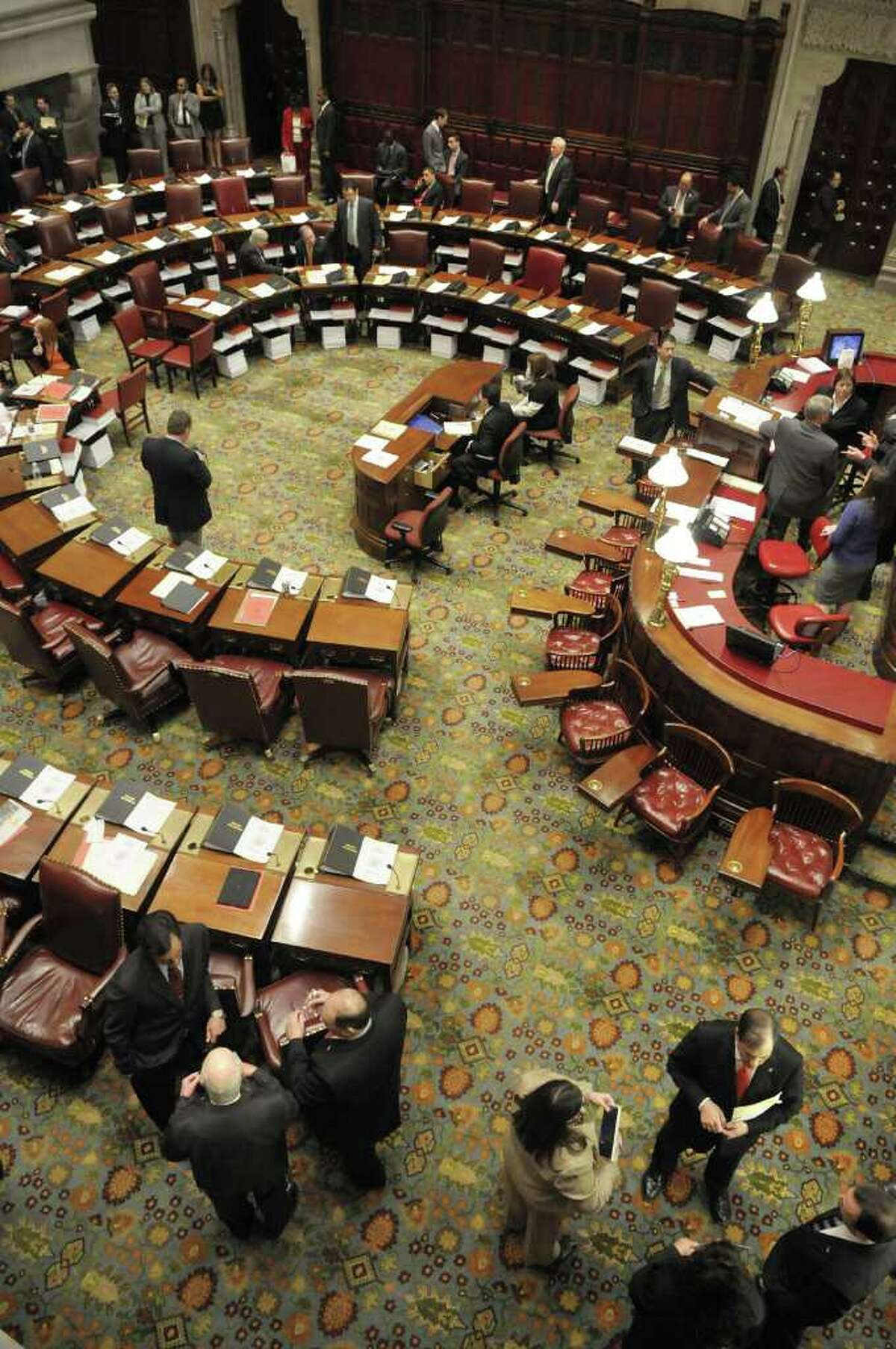 Senators and staff talk on the floor of the New York State Senate before the start of a Senate session on Tuesday, March 29, 2011. The stacks of paper beneath the Senator' desks contain budget bills that will be voted on. (Paul Buckowski / Times Union)