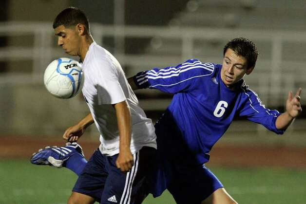 New Braunfels' John O'Brien (06) passes the ball around Roosevelt's Erik Nino (left) in boys soccer at Comalander Stadium on Tuesday, March 29, 2011. Photo: Kin Man Hui/kmhui@express-news.net / San Antonio Express-News NFS