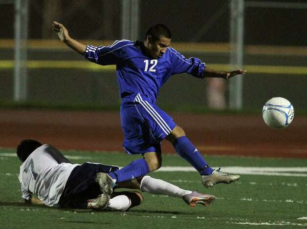 New Braunfels' Jose Gutierrez (12) takes a shot against Roosevelt's Amhir Carrillo (07) in boys soccer at Comalander Stadium on Tuesday, March 29, 2011. Photo: Kin Man Hui/kmhui@express-news.net / San Antonio Express-News NFS