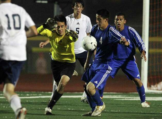 Roosevelt goalkeeper Vincent Barretto (second from left) attempts to block a shot attempt by New Braunfels' Sergio Mendez (04) in boys soccer at Comalander Stadium on Tuesday, March 29, 2011. Photo: Kin Man Hui/kmhui@express-news.net / San Antonio Express-News NFS