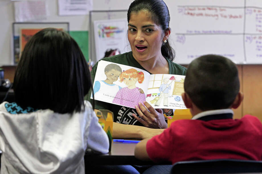 Irma Munoz works with Jackie Sanchez and Roy Dominguez in the Communities in Schools program at Mead Elementary. Students in the program might speak any of 35 languages and some of the children are political refugees. Photo: Tom Reel/treel@express-news.net / © 2011 San Antonio Express-News