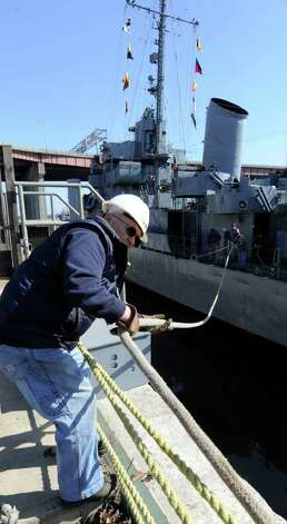 Another sign of spring: the USS Slater moves to the Albany side of the port  from its winter dock on the Rensselaer side of the Hudson River on March 30, 2011.  Volunteer deckhand Dave Mardon pulls in a rope to assist in securing the ship. (Skip Dickstein / Times Union) Photo: SKIP DICKSTEIN / 2008