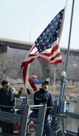 Another sign of spring: the USS Slater moves to the Albany side of the port  from its winter dock on the Rensselaer side of the Hudson River on March 30, 2011. Volunteer Chris Lecce raises the American flag on the ship.  (Skip Dickstein / Times Union) Photo: SKIP DICKSTEIN / 2008