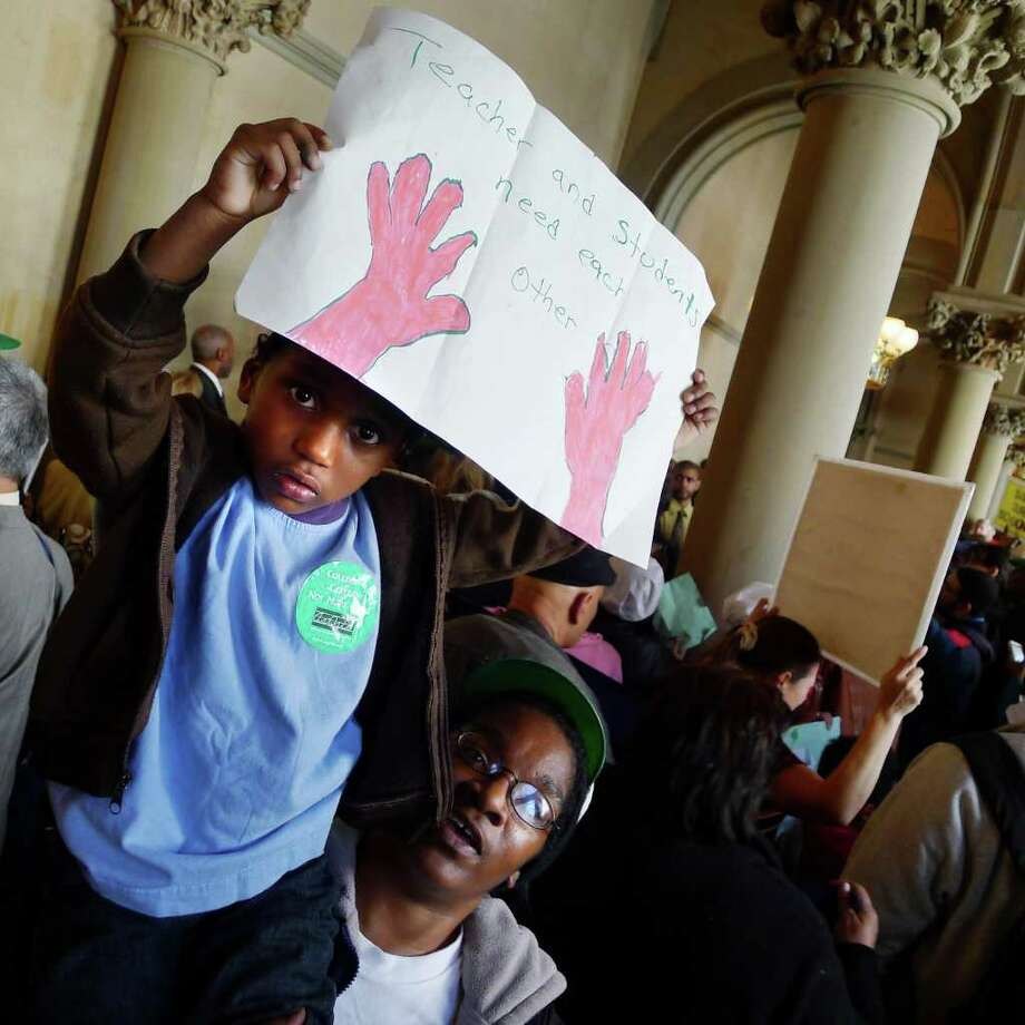 Cathy Chandler of Long Island holds her three-year-old son Kory Chandler as he holds his hand made sign as they both protests education cuts in the New York State budget at the Capitol in Albany Wednesday March 30, 2011.( Michael P. Farrell/Times Union ) Photo: Michael P. Farrell / 00012577A