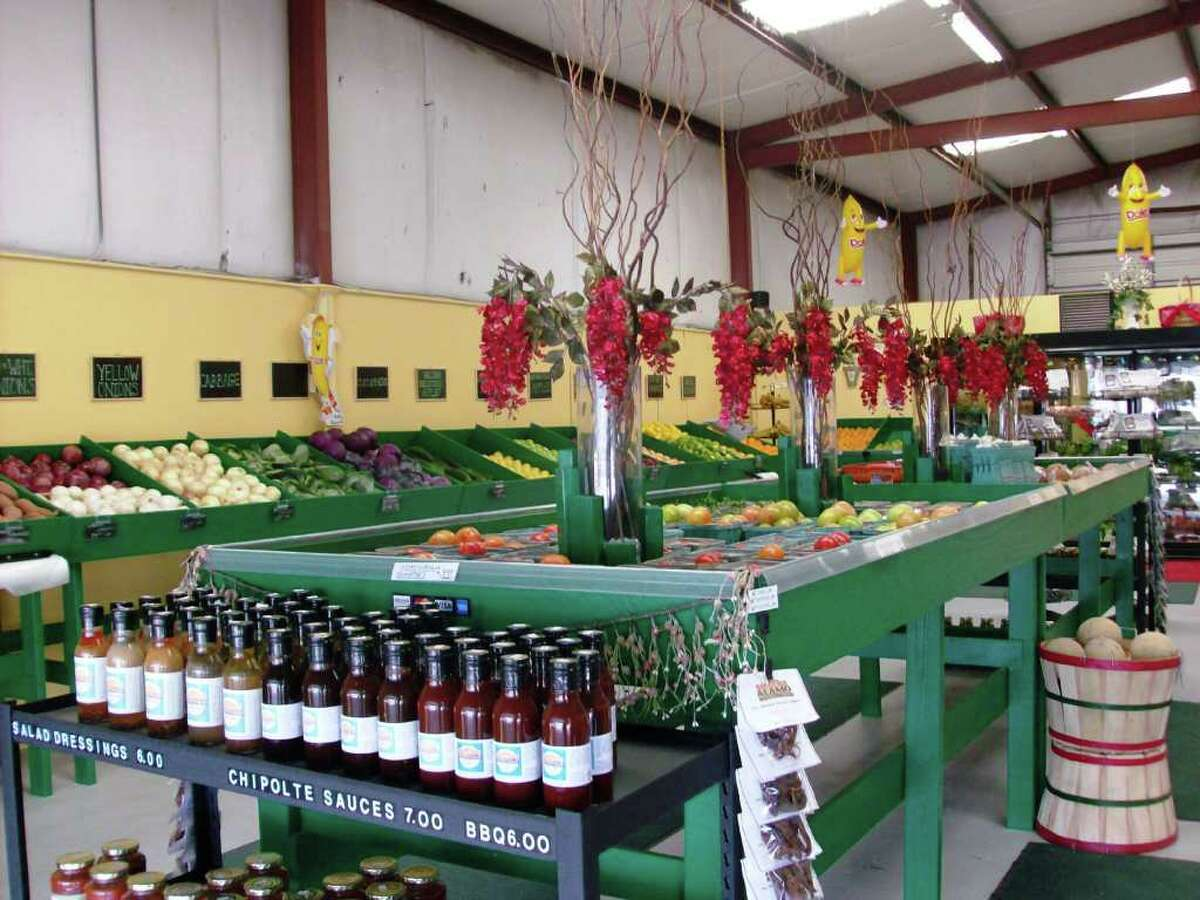 Flowers and bottles of sauce are surrounded by bins of fresh vegetables at Rocco's Farmers Market in Converse.