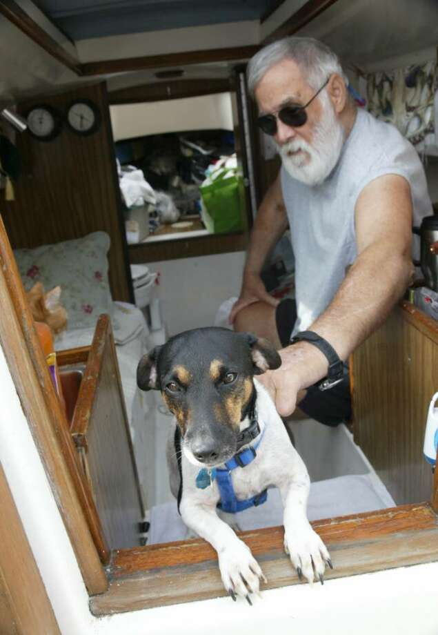 "Chris Yarbrough, from Tifton, Ga., along with ""Greenie"",  sit in the cabin on his 25' sailboat ""Jenny"" at Fayerweather Yacht Club in Black Rock, Ct.Yarbrough, and his wife Sandra, recently ran aground in Fairfield and needed to be rescued. Members of the Yacht Club have been helping repair and restore the boat to sea worthy condition, Tuesday, Sept. 22, 2009. Photo: Phil Noel / Connecticut Post"