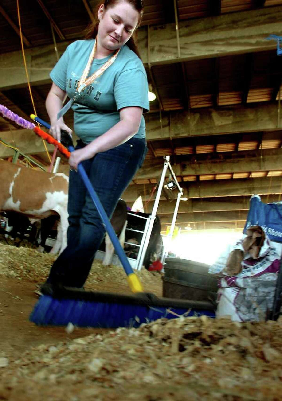 Skyler Trajan from Hamshire-Fannett High School sweeps out the walkway near her cows during the South Texas State Fair at Ford Park in Beaumont, Wednesday. Tammy McKinley/The Enterprise