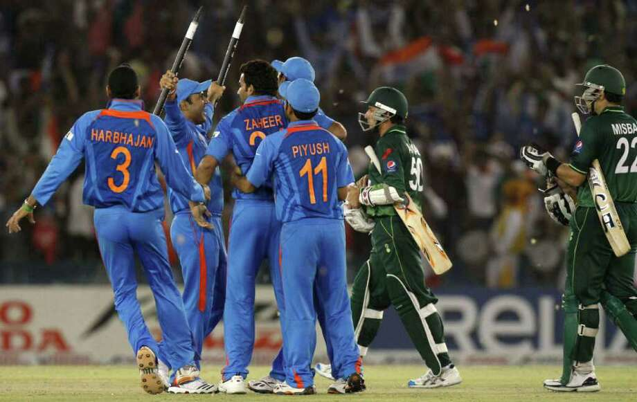 CORRECTS VICTORY MARGIN - India players celebrate their win by 29 runs, as Pakistan players, right, walk off the field following the Cricket World Cup semi-final match between Pakistan and India in Mohali, India, Wednesday, March 30, 2011. (AP Photo/Gurinder Osan) Photo: Gurinder Osan, AP / AP