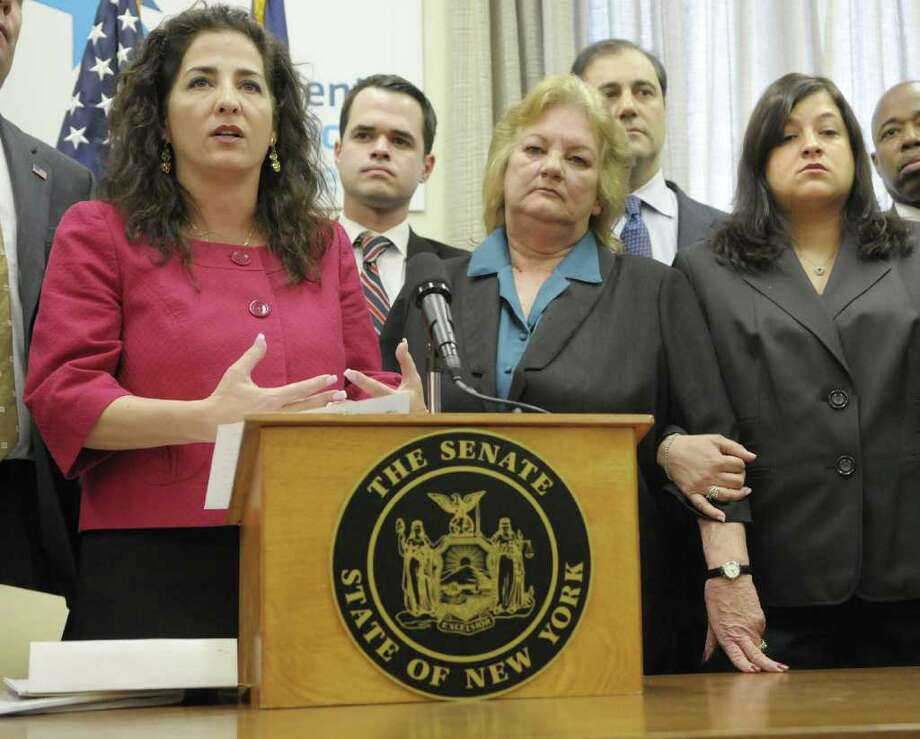 Marti Wimmer, foreground 2nd from left, and her daughter, Christina Criscitiello, far right, listen as Senator Diane Savino, left, addresses those gathered at a press conference at the Capitol in Albany, NY on Wednesday, March 30, 2011.  The press conference was held to announce legislation named after Marti's daughter, Caroline Wimmer, who was murdered in March of 2009.  The bill, would make it a felony for public servants to broadcast unauthorized crime scene images that were taken during the course of their official duties.  In 2009, an EMT that responded to the scene of Wimmer's death, then later posted a photograph he took of Wimmer on Facebook.  Senator Savino is the prime sponsor of the bill in the Senate. (Paul Buckowski / Times Union) Photo: Paul Buckowski
