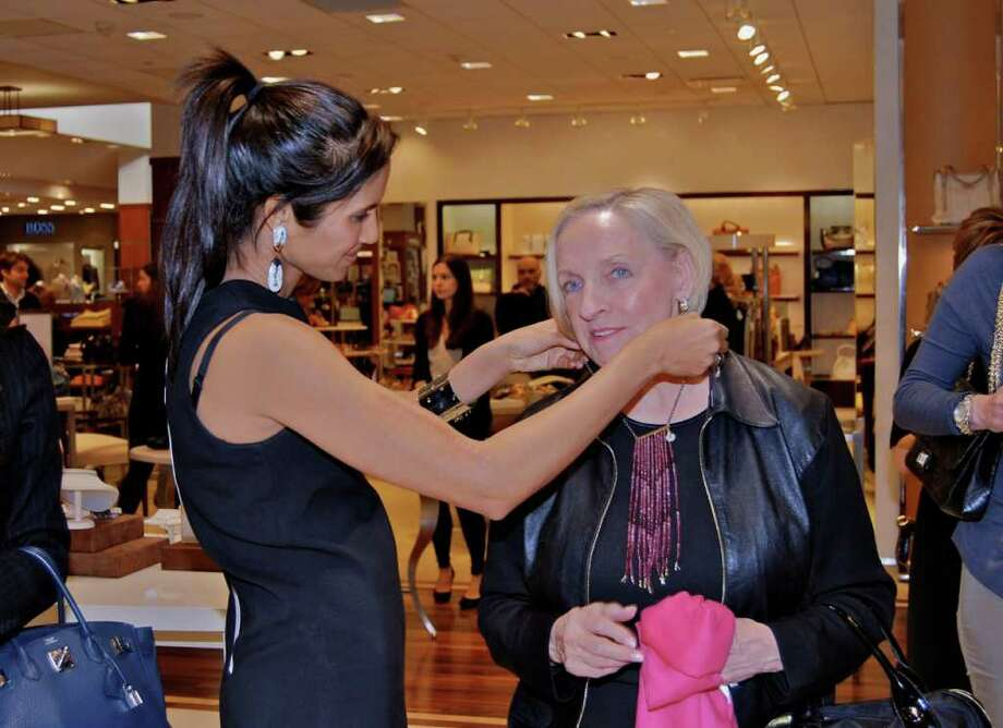 Padma Lakshmi helps Darlene Crenz try on one of her newly designed necklaces at Mitchell's of Westport. Photo: Jeanna Petersen Shepard / New Canaan News